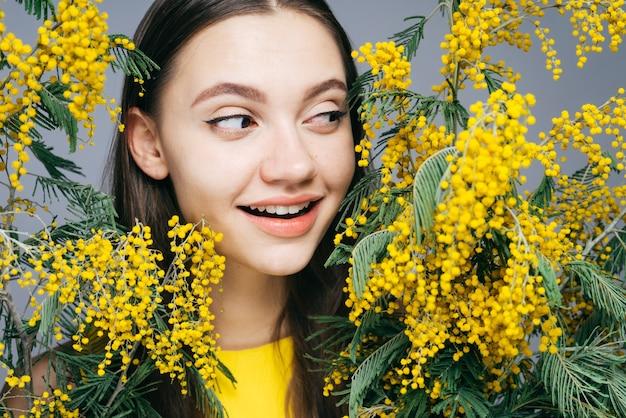 행복한 어린 소녀는 향기로운 노란색 미모사, 봄 날씨를 즐깁니다