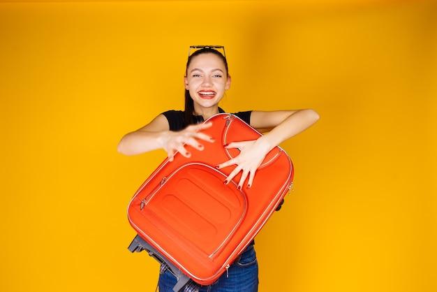 幸せな若い女の子は、大きな赤いスーツケースを持って、休暇旅行に行きます