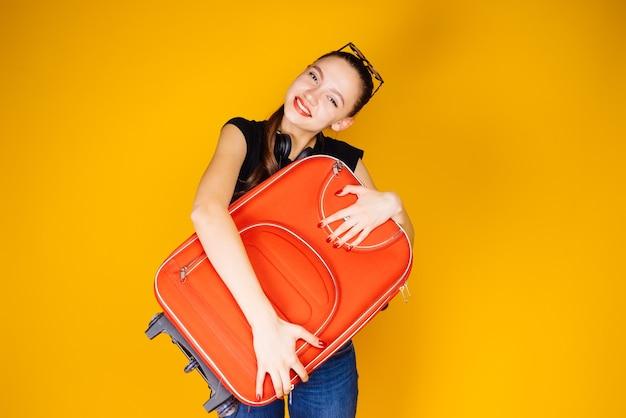 休暇、冒険、大きな赤いスーツケースを持って行く幸せな少女