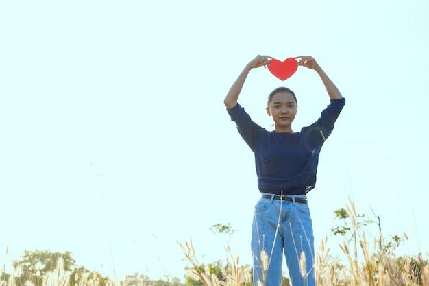 幸せな若い女の子は牧草地のアジアの女の子で紙の赤いハートを保持します