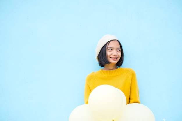 Happy young girl hold yellow balloon wear yellow sweater smile over blue background.