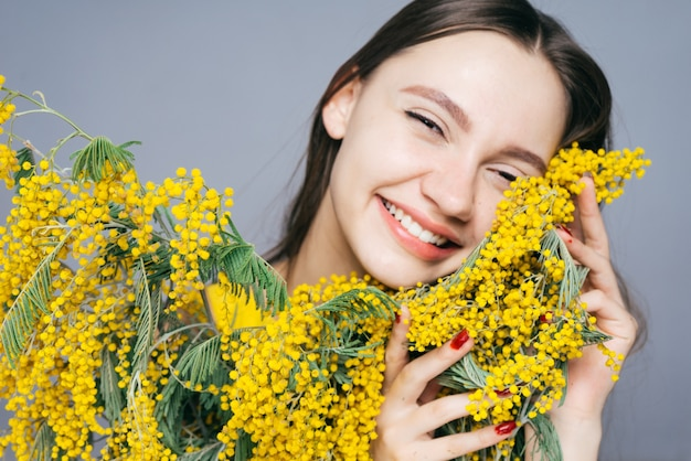 노란 미모사의 큰 꽃다발을 들고 웃고 있는 행복한 어린 소녀
