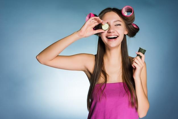 Счастливая молодая девушка держит огурец для увлажнения кожи лица на головке бигуди