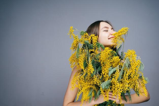 노란 미모사의 큰 꽃다발을 들고 봄과 냄새를 즐기는 행복한 어린 소녀