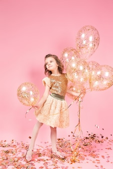 Happy young girl holding bunch of balloons