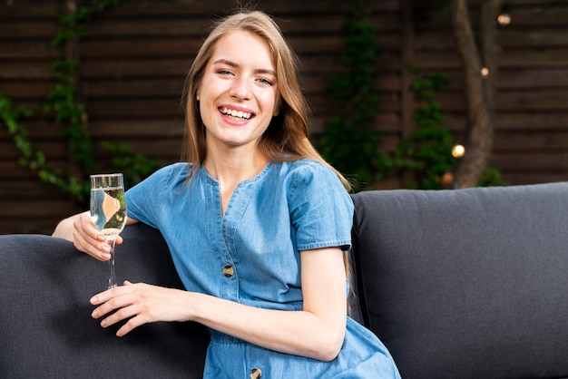 Happy young girl holding a champagne glass