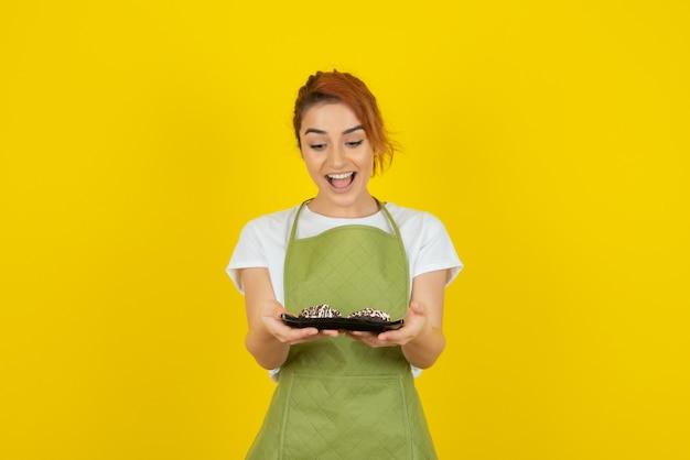 黄色の壁に新鮮な自家製クッキーを保持している幸せな少女