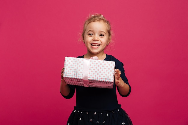 Happy young girl holding gift box and looking at camera