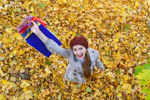 Счастливая молодая девушка, держащая хозяйственные сумки