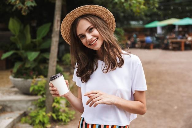 Счастливая молодая девушка держит чашку кофе на вынос, стоя в парке на открытом воздухе