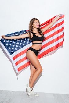 흰색 배경에 고립 된 비키니에 미국 국기를 들고 행복 한 어린 소녀