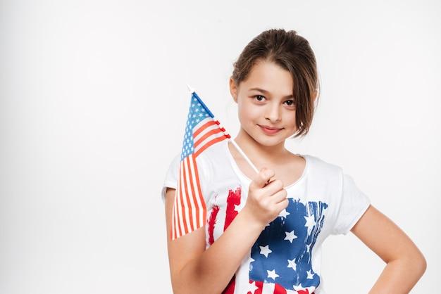 Счастливая молодая девушка держит флаг сша