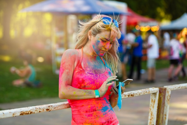 Happy young girl on holi color festival using mobile phone