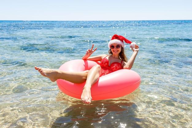 뿌려 도넛과 비스 크리스마스 모자에 행복 한 어린 소녀, 여름 선글라스와 함께 웃고, 바다에 떠있는