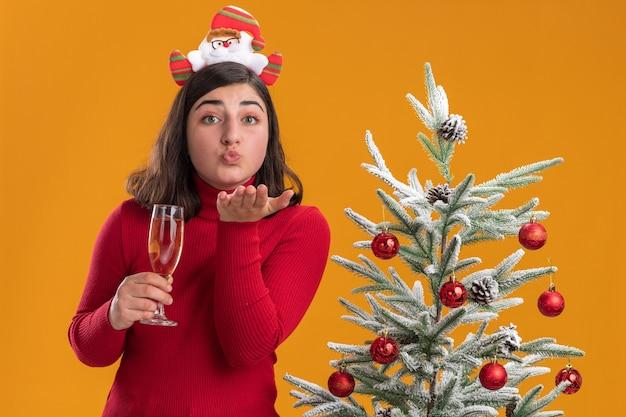 샴페인 잔을 들고 오렌지 배경 위에 크리스마스 트리 옆에 키스를 불고 재미있는 머리띠를 입고 크리스마스 스웨터에 행복 한 어린 소녀