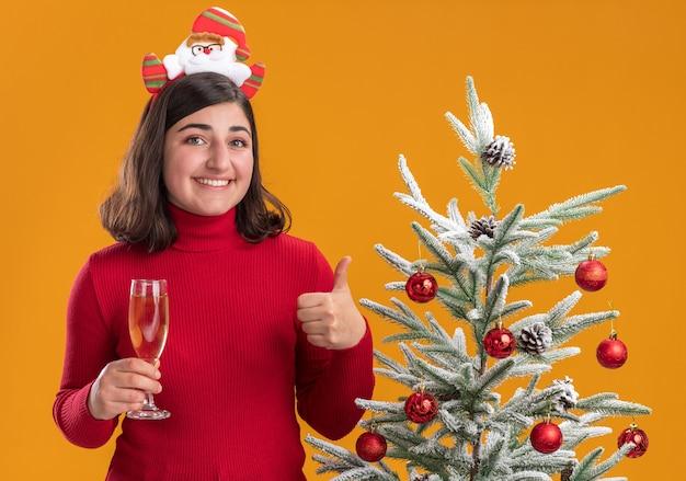 오렌지 배경 위에 크리스마스 트리 옆에 샴페인 잔을 들고 재미있는 머리띠를 입고 크리스마스 스웨터에 행복 한 어린 소녀