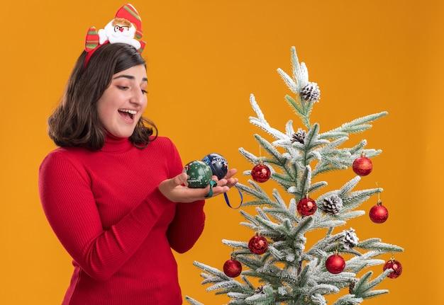 オレンジ色の背景の上のクリスマスツリーの横にx-masボールを保持している面白いヘッドバンドを身に着けているクリスマスセーターの幸せな少女