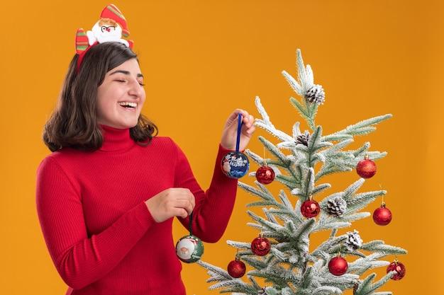 オレンジ色の背景の上のクリスマスツリーの横に面白いヘッドバンドを身に着けているクリスマスセーターの幸せな少女