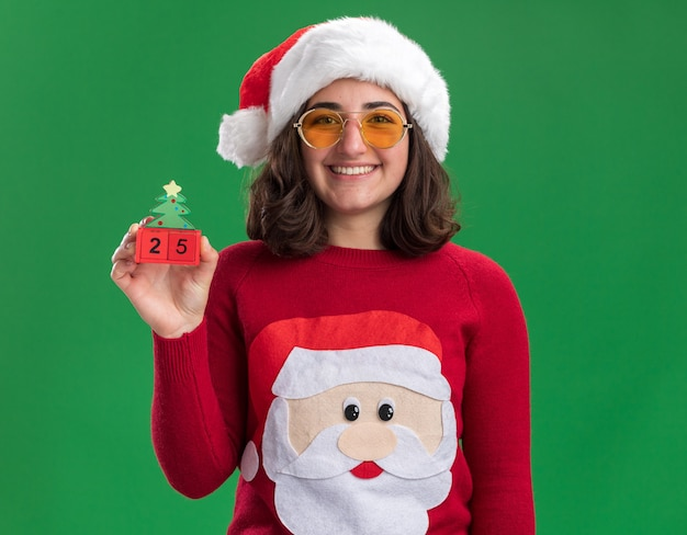 Счастливая молодая девушка в рождественском свитере, шляпе санта-клауса и очках, держит игрушечные кубики с номером двадцать пять с улыбкой на лице, стоя над зеленой стеной
