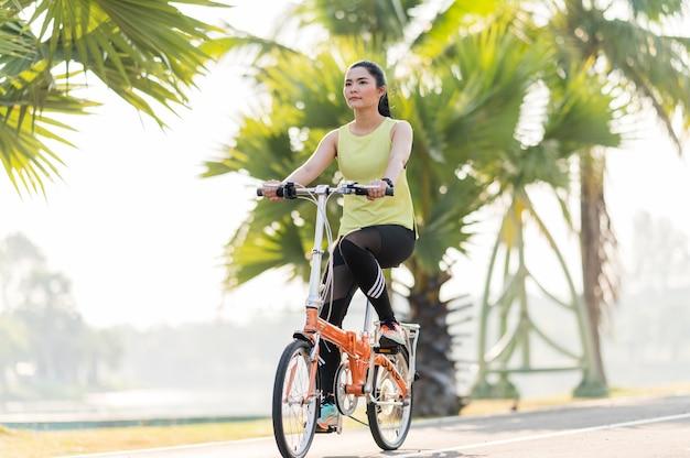 公園で自転車と緑のドレスの幸せな少女