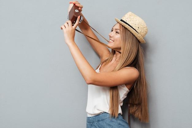 회색 배경에 고립 된 레트로 카메라로 셀카를 만드는 모자에 행복 한 어린 소녀