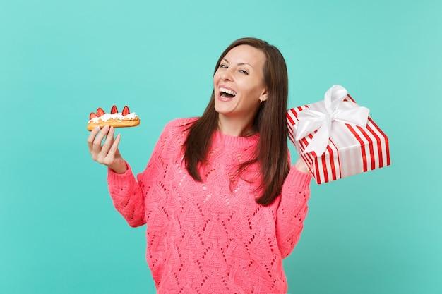 青い背景で隔離のギフトリボンとエクレアケーキ赤い縞模様のプレゼントボックスを保持しているニットピンクのセーターの幸せな少女。バレンタインの女性の日の誕生日の休日の概念。コピースペースをモックアップします。