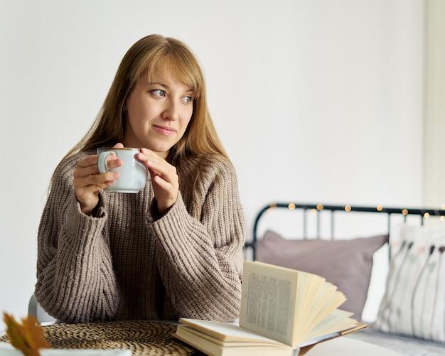 Счастливая молодая девушка в свитере мечтает с чашкой чая во время чтения книги в спальне