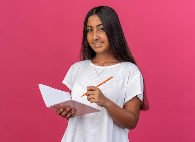 흰색 티셔츠를 입은 행복한 어린 소녀가 노트북과 연필을 들고 분홍색 배경 위에 서 있는 얼굴에 미소를 띠고 카메라를 바라보고 있습니다.