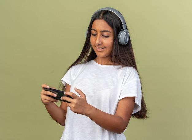 Счастливая молодая девушка в белой футболке с наушниками на голове играет в игру, используя свой смартфон улыбается