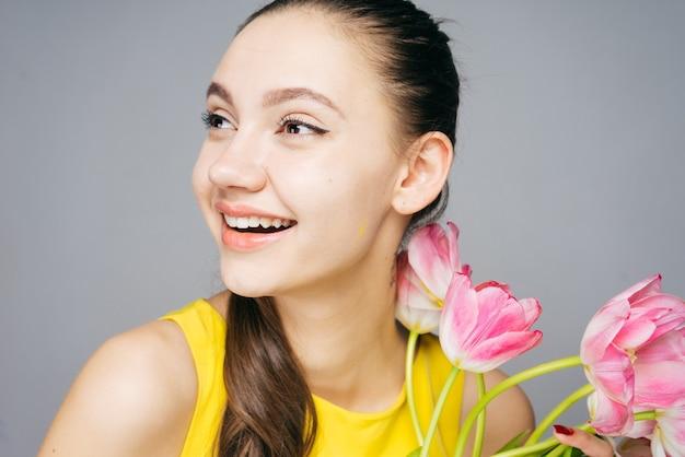 노란 드레스를 입은 행복한 어린 소녀는 봄에 기뻐하고 분홍색 꽃 꽃다발을 들고 있다