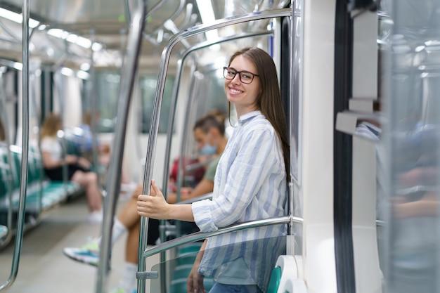 지하철 객차 안에 있는 행복한 어린 소녀가 대학에서 성공적인 시험을 마치고 집으로 돌아옵니다