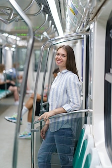 지하철 객차 안에 있는 행복한 어린 소녀가 대학 시험을 마치고 집으로 돌아옵니다