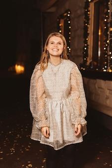 Счастливая молодая девушка улыбается в камеру возле кафе, украшенного на рождество.