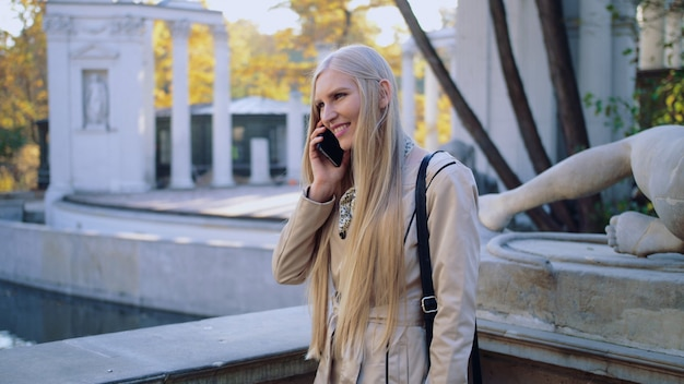 A happy young girl is talking on a mobile phone in the autumn park of the city