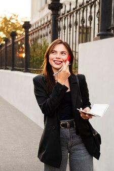 幸せな若い女の子が携帯電話で話していると笑顔です。