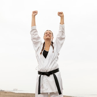 Happy young girl in karate costume