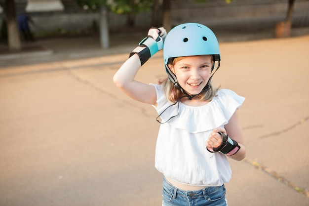 Happy young girl knocking on sports helmet she is wearing outdoors, copy space