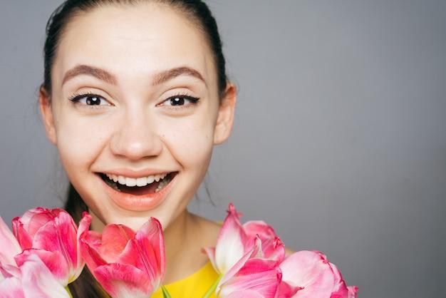 행복한 어린 소녀가 웃고, 향기로운 분홍색 꽃 꽃다발을 들고 있다