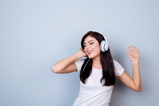 Happy young girl listening to music in headphones and dancing