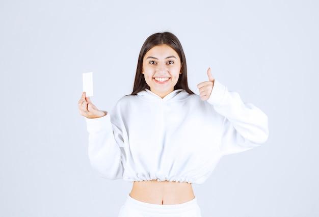 Modello di ragazza felice con una carta che mostra un pollice in su.