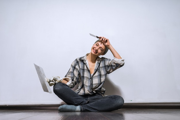 Счастливый молодой художник-девушка сидит на полу, устал делать ремонт, вытирает пол со лба