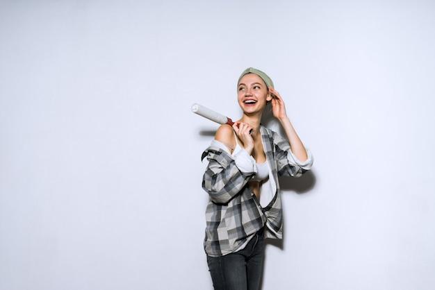 幸せな少女がローラーで壁を白く塗って笑う