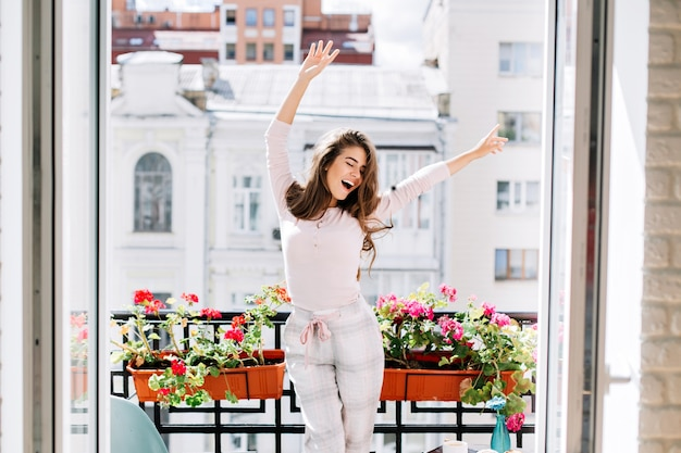 Happy young girl in pajamas having fun on balcony in sunny morning. she raises hands and keeps eyes closed.