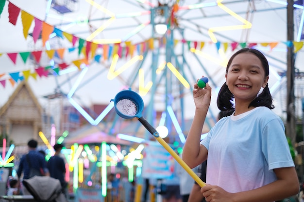 Happy young girl playing game at night market.