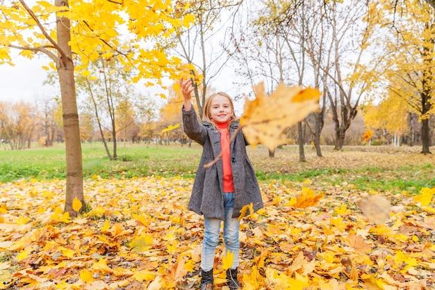 자연의 아름다운 가을 공원에서 떨어지는 노란 잎 아래에서 놀고 있는 행복한 어린 소녀가 야외에서 산책합니다. 어린 아이가 가을 주황색 단풍잎을 던졌습니다.