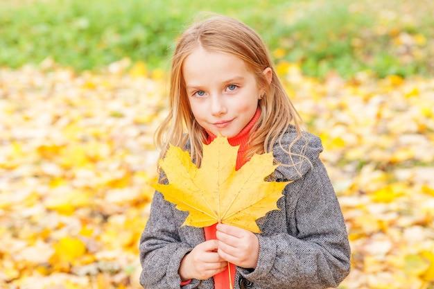 자연의 아름다운 가을 공원에서 떨어지는 노란 잎을 가지고 노는 행복한 어린 소녀는 야외에서 산책합니다. 가 오렌지 메이플 리프를 들고 작은 아이.