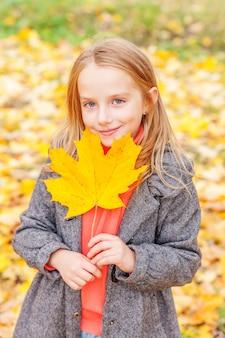 Счастливая молодая девушка играет с падающими желтыми листьями в красивом осеннем парке на прогулках на природе