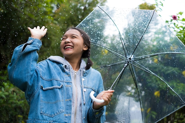 Happy young girl playing with rain in green garden.