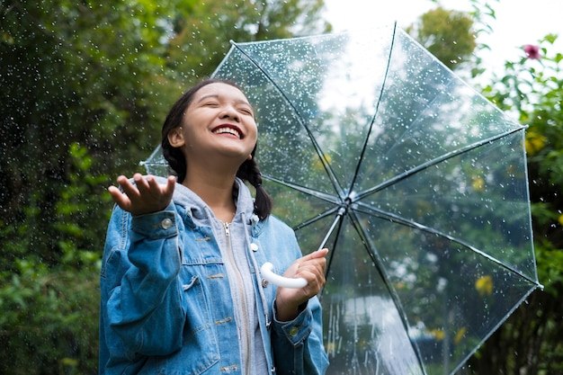 緑の庭で雨と遊ぶ幸せな少女。