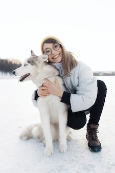 冬の公園でシベリアンハスキー犬と遊んで幸せな若い女の子